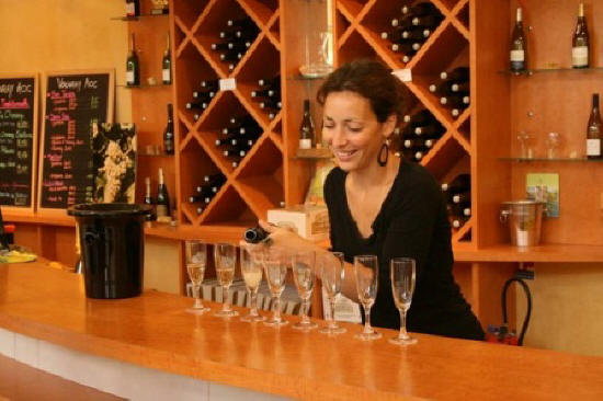 young woman pouring sparkling Vouvray wine to taste